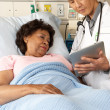 Stock Photo: Doctor Using Digital Tablet Talking With Senior Patient