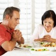 Stock Photo: Senior Couple Saying Grace Before Meal At Home