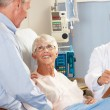 Stock Photo: Doctor Talking To Senior Couple On Ward