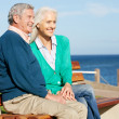 Senior Couple Sitting On Bench By Sea Together — Stock Photo