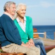 Stock Photo: Senior Couple Sitting On Bench By Sea Together