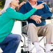 Senior Woman Pushing Husband In Wheelchair — Stock Photo #24647489