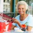 Senior Couple Enjoying Snack At Outdoor Cafe After Shopping — Stock Photo #24647665