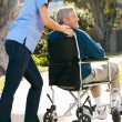 Carer Pushing Senior Man In Wheelchair - Stock Photo