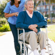 Carer Pushing Senior Man In Wheelchair — Stock Photo #24647861
