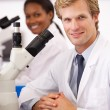 Male And Female Scientists Using Microscopes In Laboratory — Foto de Stock