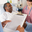 Doctor Looking At Chart With Senior Male Patient — Stock Photo