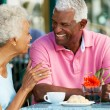 Stock Photo: Senior Couple Enjoying Snack At Outdoor Cafe