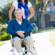 Adult Daughter Pushing Senior Father In Wheelchair — Stock Photo #24648195