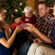 Family Opening Presents In Front Of Christmas Tree — Photo