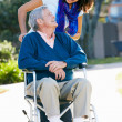 Stock Photo: Adult Daughter Pushing Senior Father In Wheelchair