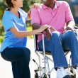 Stockfoto: Carer Pushing Senior MIn Wheelchair
