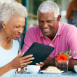 Senior Couple Using Tablet Computer At Outdoor Cafe — Stock Photo