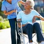 Carer Pushing Senior Woman In Wheelchair — Stock Photo