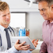 Doctor Discussing Records With Patient Using Digital Tablet — Stock Photo #24648619