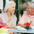 Senior Couple Enjoying Snack At Outdoor Cafe After Shopping — Stock Photo #24648709
