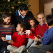 Multi Generation Family Opening Christmas Presents In Front Of T — Stock Photo