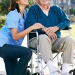 Stock Photo: Carer Pushing Senior MIn Wheelchair