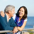 Senior Man With Adult Daughter Looking Over Railing At Sea - Foto Stock