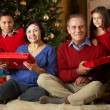 Grandparents With Grandchildren In Front Of Christmas Tree — Stock Photo