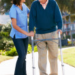 Carer Helping Senior Man With Walking Frame - Stock Photo