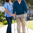 Carer Helping Senior Man With Walking Frame — Stock Photo