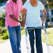 Senior Man Helping Wife With Walking Frame - Stock Photo