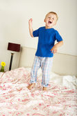 Young Boy Bouncing On Bed — Stock Photo