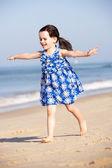 Klein meisje loopt langs de strand — Stockfoto