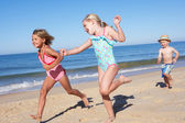 Three Children Running Along Beach — Stock Photo
