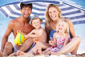 Family Sheltering From Sun Under Beach Umbrella — Стоковое фото