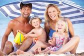 Familia refugiarse del sol bajo la sombrilla de playa — Foto de Stock