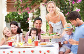 Woman Serving Meal To Two Families — Stock Photo