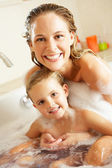 Mother And Daughter Relaxing In Bubble Filled Bath — Stock Photo
