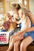 Madre e figli l'ordinamento lavanderia seduta sul bancone della cucina — Foto Stock