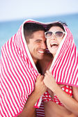 Couple Sheltering From Sun On Beach Holiday — Stock Photo