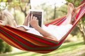 Mulher sênior relaxante numa rede com e-book — Foto Stock