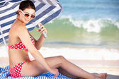 Woman Sheltering From Sun Under Beach Umbrella Putting On Sun Cr — Stock Photo