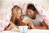 Couple Snuggled Under Duvet Eating Breakfast — Foto de Stock