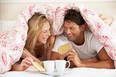 Couple Snuggled Under Duvet Eating Breakfast — Stock Photo
