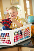 Boy Sitting In Basket Sorting Laundry On Kitchen Counter — Stock Photo