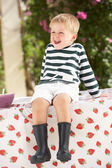 Young Boy Wearing Wellington Boots Sitting On Table — Stock Photo
