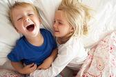 Hermano y hermana relajarse juntos en la cama — Foto de Stock