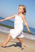 Küçük kız plaj boyunca çalışan — Stok fotoğraf