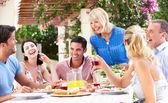 Gruppe von jugendlichen und senioren paare genießen mahlzeit in der familie — Stockfoto