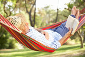 Senior Man Relaxing In Hammock With Book — Stock Photo