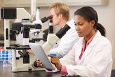 Científicos usando microscopios y tableta digital en laboratorio — Foto de Stock