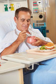 Male Patient Enjoying Meal In Hospital Bed — Stock Photo