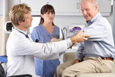 Doctor Examining Male Patient With Elbow Pain — Stockfoto