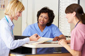 Doctor And Nurses In Discussion At Nurses Station — Stockfoto